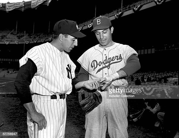 Shortstop Phil Rizzuto of the New York Yankees inspects the brace on the left hand of outfielder Carl Furillo of the Brooklyn Dodgers prior to a 1955...