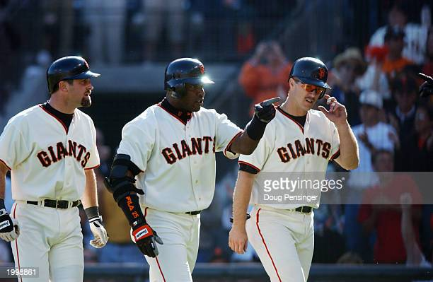 Shortstop Rich Aurilia left fielder Barry Bonds and second baseman Jeff Kent of the San Francisco Giants walk to the dugout after Barry Bonds' three...