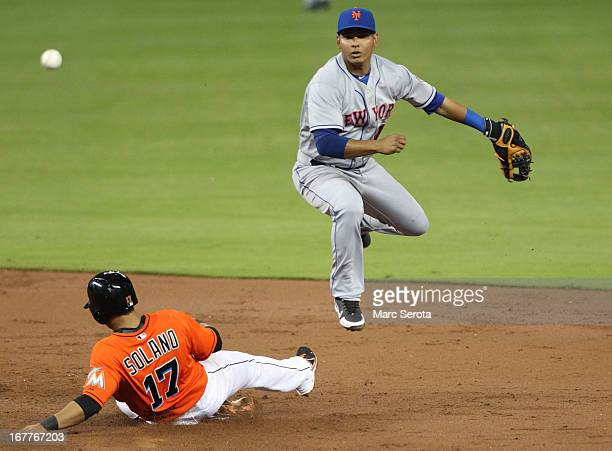 Shortstop Ruben Tejada of the New York Mets turns a double play against Donovan Solano of the Miami Marlins at Marlins Park on April 29 2013 in Miami...