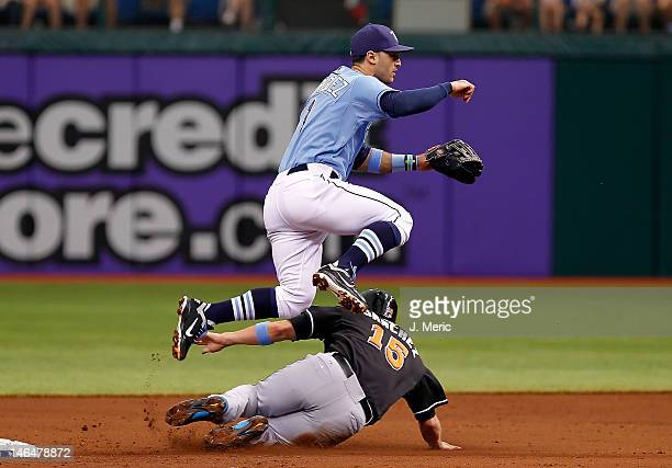 Shortstop Sean Rodriguez of the Tampa Bay Rays turns a double play as infielder Gaby Sanchez of the Miami Marlins tries to break it up during the...