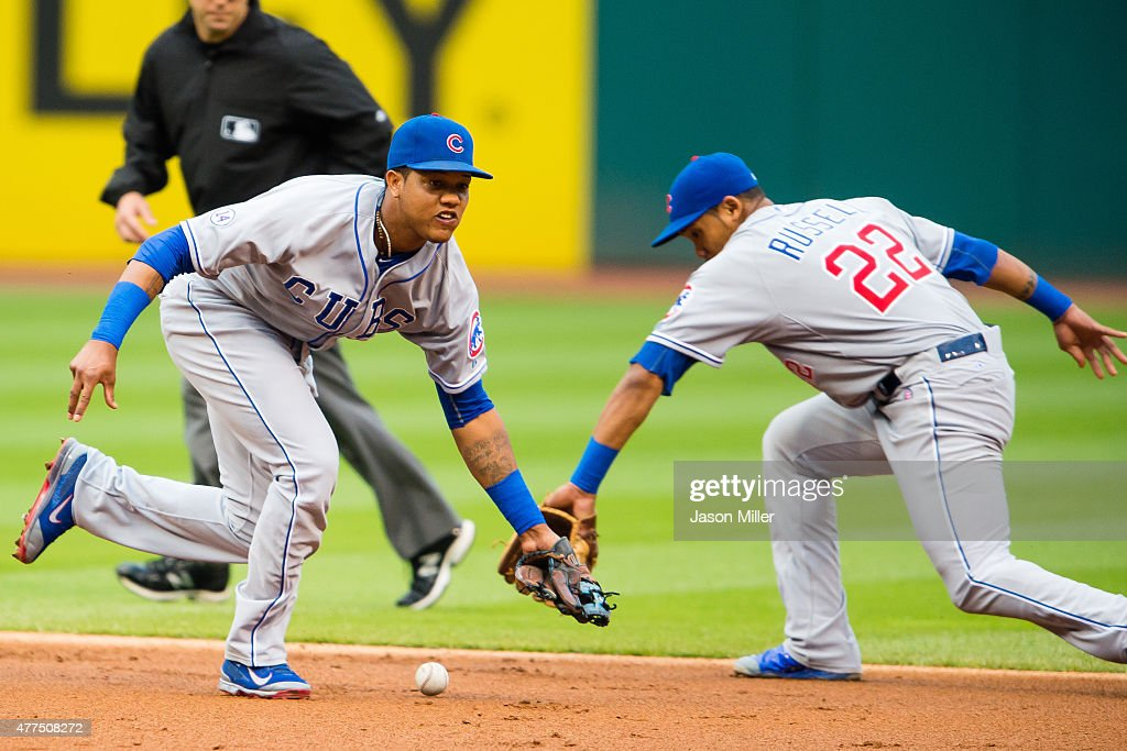 Shortstop Starlin Castro #13 misses a ground ball hit by Michael Brantley #23 of the Cleveland Indians during the first inning with backup from second baseman Addison Russell #22 of the Chicago Cubs at Progressive Field on June 17, 2015 in Cleveland, Ohio.