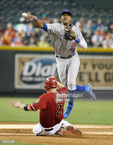 Shortstop Starlin Castro of the Chicago Cubs leaps to avoid the slide of Aaron Hill of the Arizona Diamondbacks as he tries to turn a double play...