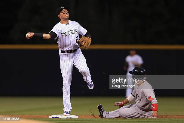Shortstop Troy Tulowitzki of the Colorado Rockies gets a force out on Shane Victorino of the Boston Red Sox but was unable to complete the double...