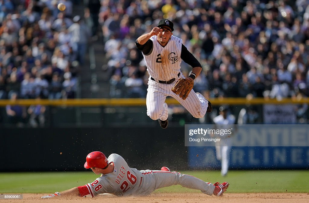 Shortstop Troy Tulowitzki #2 of the Colorado Rockies turns a double play on Chase Utley #26 of the Philadelphia Phillies on a grounder hit by Ryan Howard to Clint Barmes in the eighth inning of MLB action on Opening Day at Coors Field on April 10, 2009 in Denver, Colorado. The Rockies defeated the Phillies 10-3.