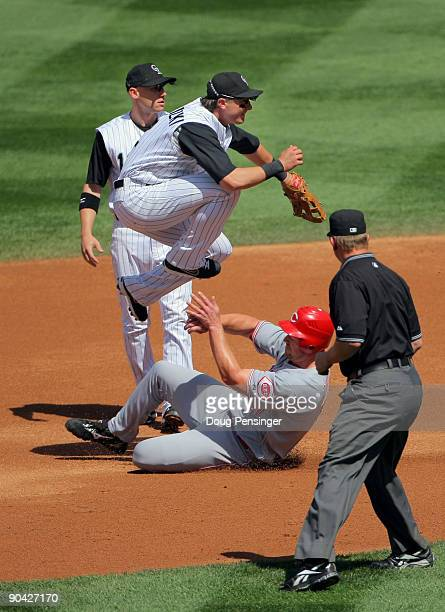 Shortstop Troy Tulowitzki of the Colorado Rockies turns a double play on Scott Rolen of the Cincinnati Reds on a ball hit by Jonny Gomes to second...