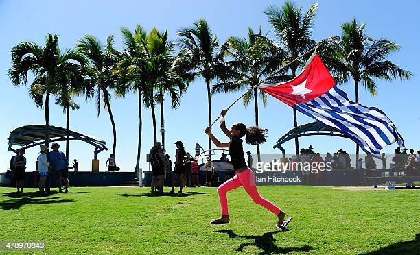 Shoshana Finlan runs with the West Papuan flag to demonstrate against the Abbott led Coalition Government on March 16 2014 in Townsville Australia...