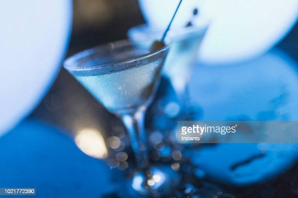 shot at night in nassau, in blue light, two dirty martinis with olives standing among ice cubes. - martini glass stock photos and pictures