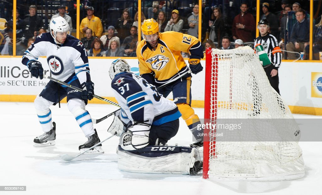 A shot by James Neal #18 of the Nashville Predators (not pictured) finds the net for the game winner in overtime as Mike Fisher #12 battles against Ben Chiarot #7 and Connor Hellebuyck #37 of the Winnipeg Jets during an NHL game at Bridgestone Arena on March 13, 2017 in Nashville, Tennessee.