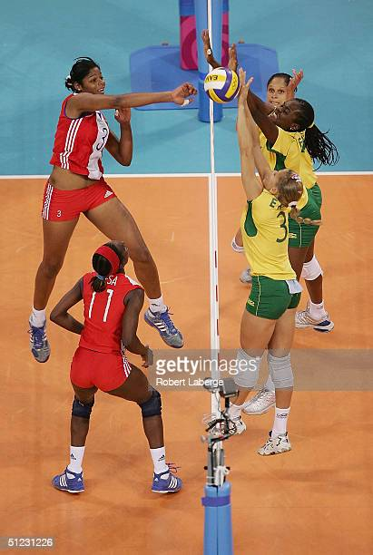 A shot by Nancy Carrillo de la Paz of Cuba is blocked by Valeska Menezes and Erika Coimbra of Brazil in the women's indoor Volleyball bronze medal...