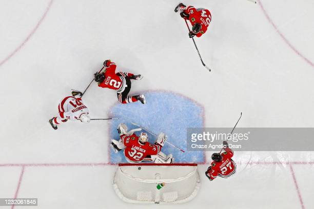 Shot by Warren Foegele of the Carolina Hurricanes enters the net past Kevin Lankinen of the Chicago Blackhawks for a goal in the second period at the...