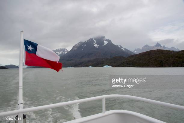 shot from back of tour boat of chilean flag with icebergs and dramatic mountains in background. - bandiera del cile foto e immagini stock