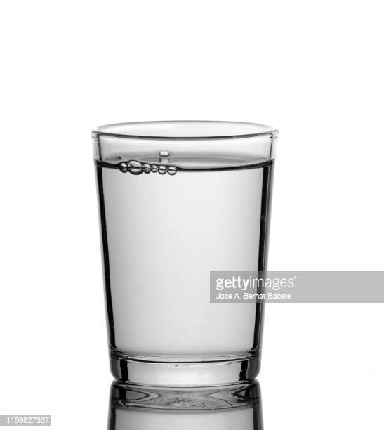 shot glass filled with water isolated on white. - drinking glass stock pictures, royalty-free photos & images