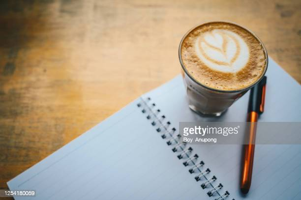a shot glass of hot latte coffee on wooden table. - coffee break stock pictures, royalty-free photos & images