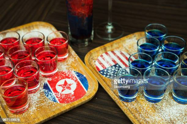Shot glasses filled with a red sojubased cocktail for North Korea left and a blue bourbonbased cocktail for US are arranged for a photograph at the...