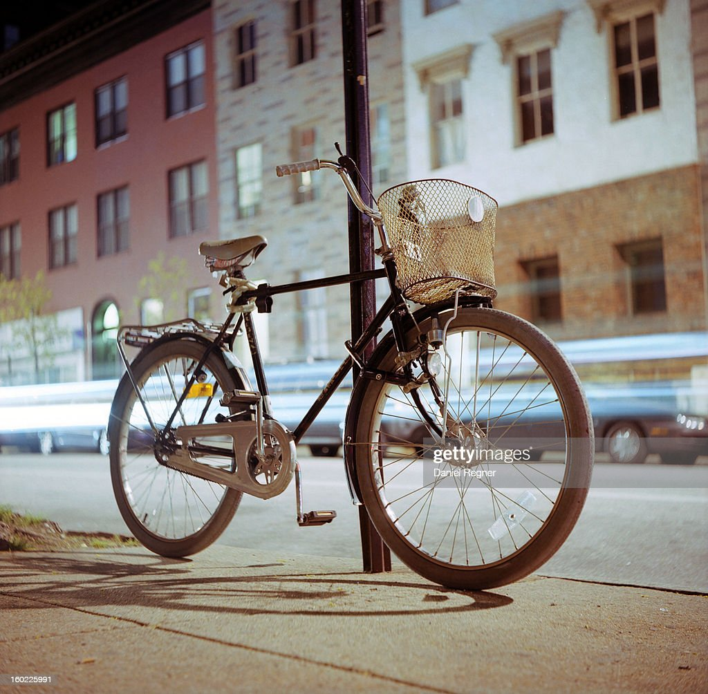 CONTENT] A shot of a bike in the city, locked up to a pole. Commuter bike in the cold of the night, with headlights passing by in a city center. Great shot to talk about the benefits of bike vs. car travel.