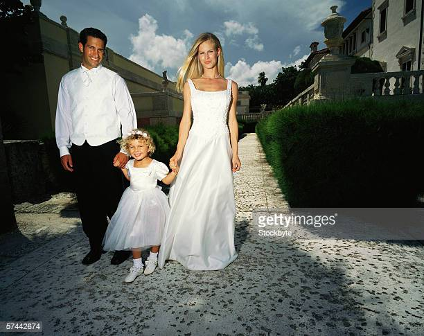shot of a bride and groom walking in a garden with a girl (6)