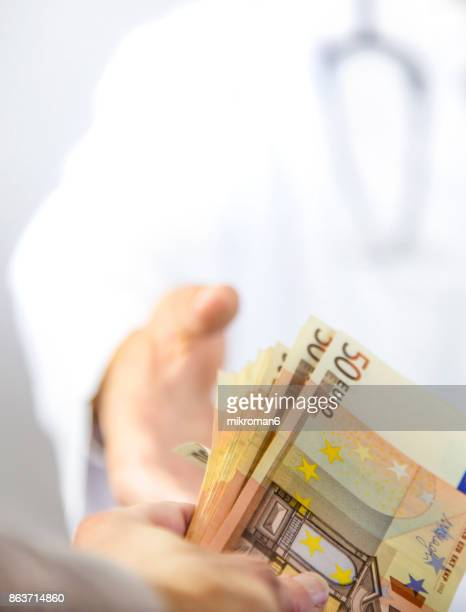 Shot of a corrupt doctor taking a bribe from patient. Medical concept