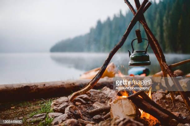 湖の近くのキャンプ場でかわいいヴィンテージティーポットのショット。 - キャンプファイヤー ストックフォトと画像