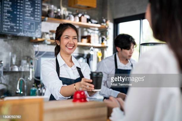 shot of a female barista serving a cup of coffee to a customer in a cafe counter. small business owner, service mind and customer service. - customer stock pictures, royalty-free photos & images