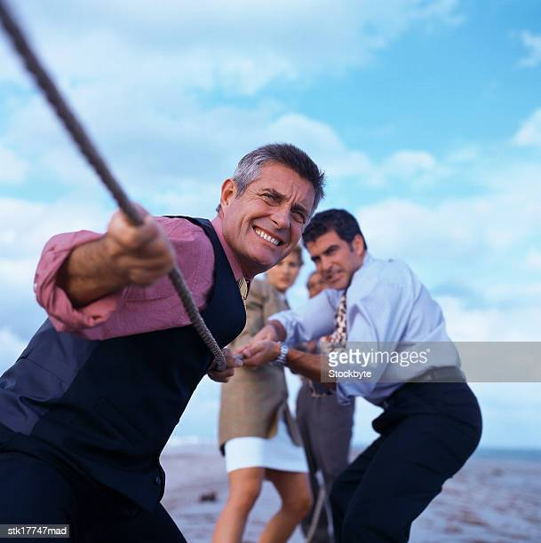 shot of a group of business executives playing tug of war
