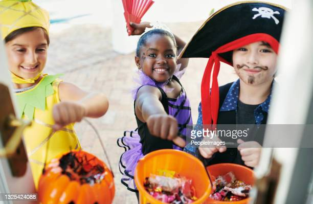shot of a group of little children going trick-or-treating - trick or treat stock pictures, royalty-free photos & images