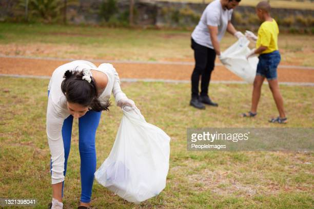 shot of a group of people picking up trash in a park - picking up stock pictures, royalty-free photos & images