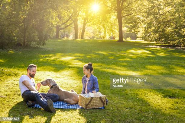 Shot of a happy father with teenage daughter and dog lying on a blanket in a park