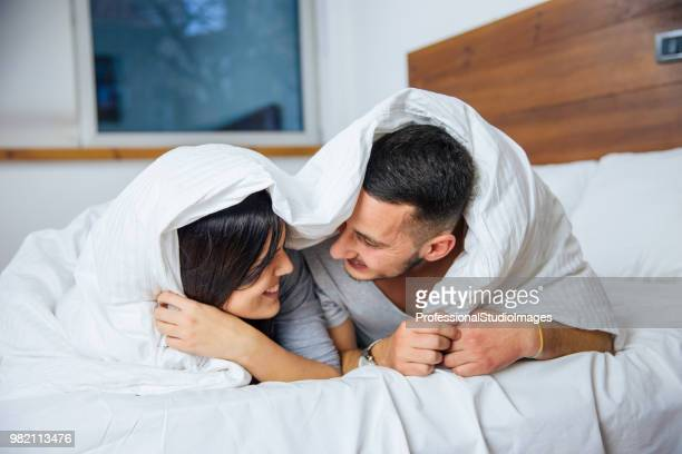Shot of a happy young couple laying under a duvet together in bed