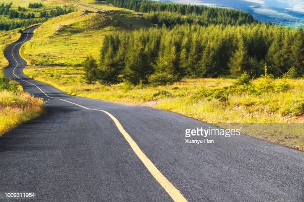shot of a long open road stretching out far away into the distance - hill stock pictures, royalty-free photos & images