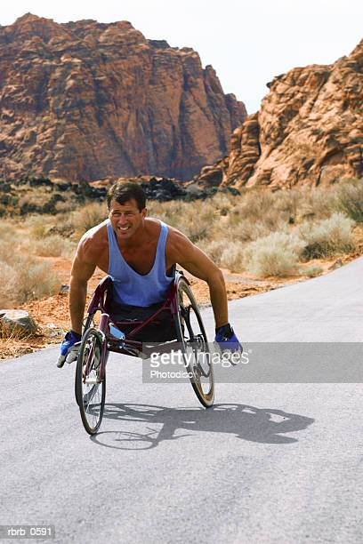 shot of a male caucasian wheelchair racer as he trains in a rural red rock setting