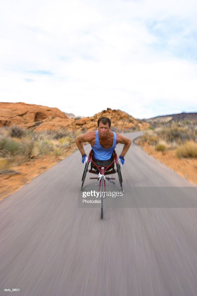 shot of a male caucasian wheelchair racer as he trains in a rural red rock setting : Stockfoto