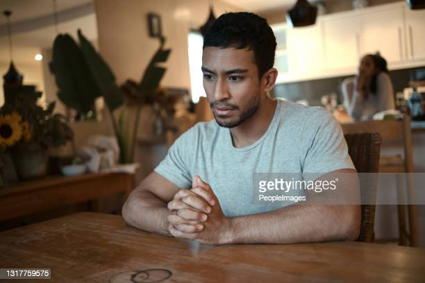 shot of a man looking stressed while sitting at home with his girlfriend standing in the background - blame stock pictures, royalty-free photos & images
