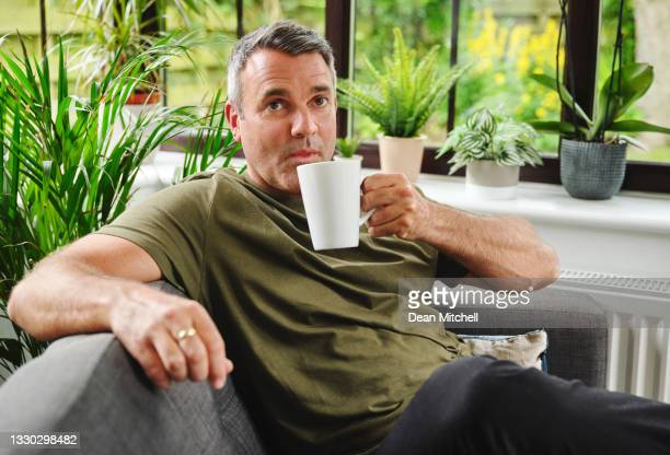 shot of a mature man having a relaxing coffee break on the sofa at home - drink stock pictures, royalty-free photos & images