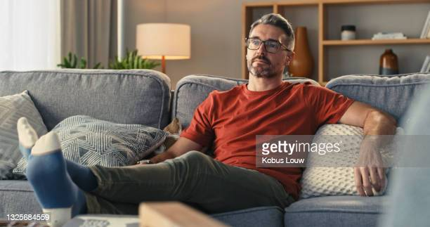 shot of a mature man relaxing on the sofa at home - loneliness stock pictures, royalty-free photos & images