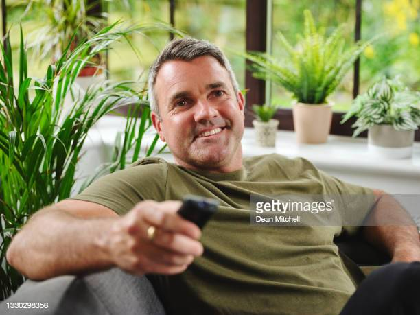 shot of a mature man watching tv on the sofa at home - entertainment event stock pictures, royalty-free photos & images