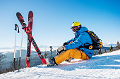 Shot of a professional skier sitting on top of the mountain near his skiing equipment relaxing enjoying beautiful snowy mountains view people living enjoyment recreation travelling riding