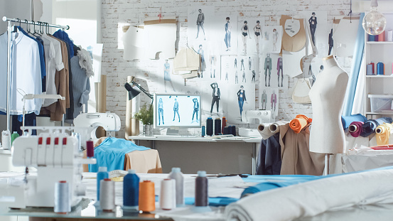 Shot of a Sunny Fashion Design Studio. We See Working Personal Computer, Hanging Clothes, Sewing Machine and Various Sewing Related Items on the Table, Mannequins Standing, Colorful Fabrics. 923796498