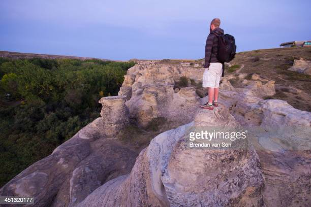 Shot of a tourist on hoodoos in Writing on Stone Provincial Park, in Southern Alberta, Canada