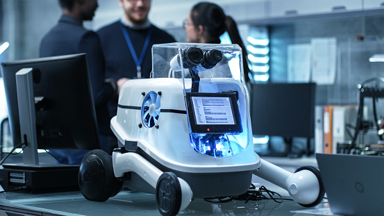Shot of a Working Robot Prototype in a Modern Laboratory/ Research Center Creating Robotics. Multiethnic Group of Young Scientists have Discussion on backgrounds. 1167549713