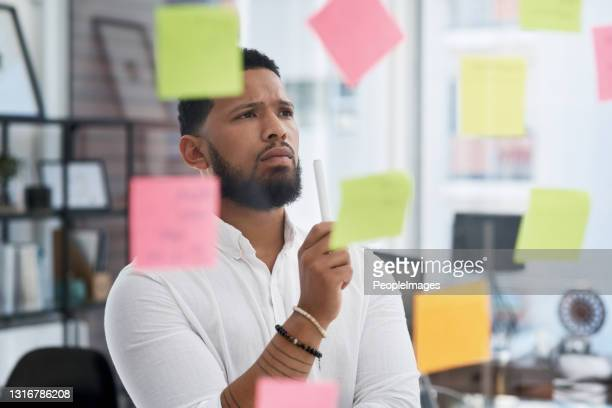 shot of a young businessman brainstorming with sticky notes on a glass wall in an office - uncertainty stock pictures, royalty-free photos & images