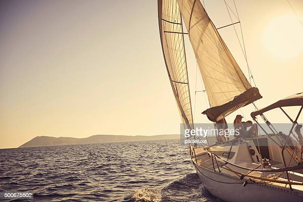 shot of a young couple spending time together on a yacht - sailor stock pictures, royalty-free photos & images
