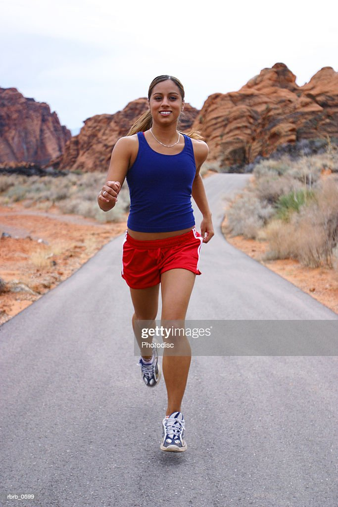 shot of a young ethnic female athlete as she runs through a rural red rock setting : Stockfoto