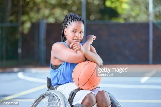 shot of a young female wheelchair basketball player on an outdoor court - basketball uniform stock pictures, royalty-free photos & images