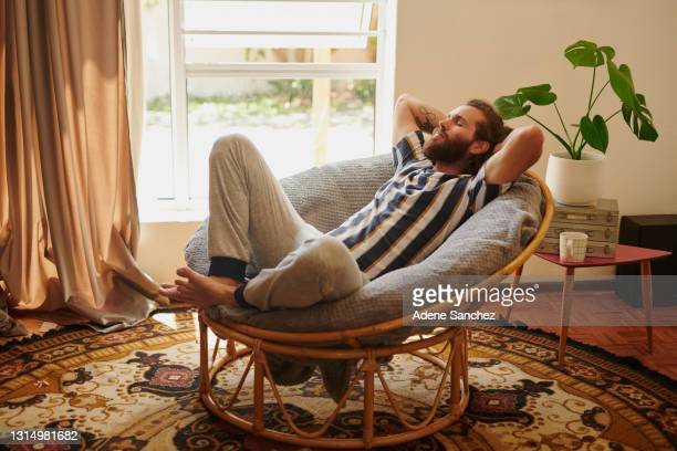shot of a young man relaxing on a chair at home - one man only stock pictures, royalty-free photos & images