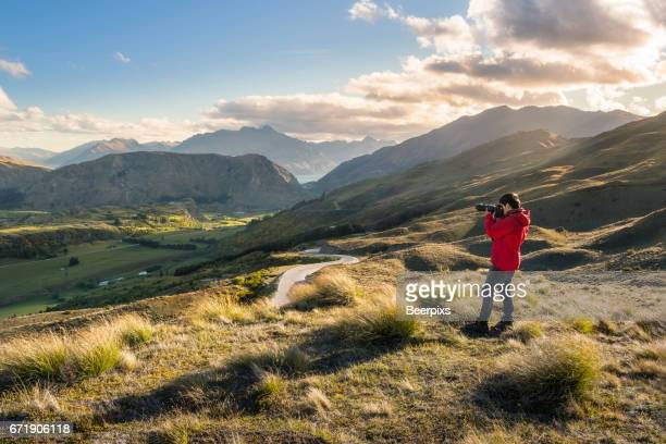 Shot of a young man taking pictures from the Coronet Peak, Queenstown, South Island of New Zealand.