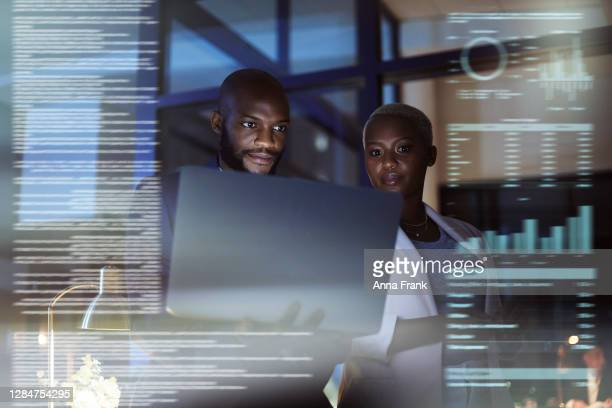 shot of a young woman and man using a laptop while working late in their office - big tech stock pictures, royalty-free photos & images