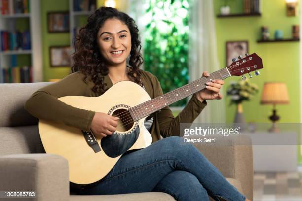shot of a young women playing guitar sitting on sofa at home:- stock photo - guitarist stock pictures, royalty-free photos & images