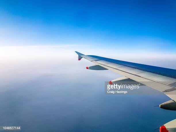shot of aircraft airplane wing through window in flight above clouds - aircraft wing stock pictures, royalty-free photos & images