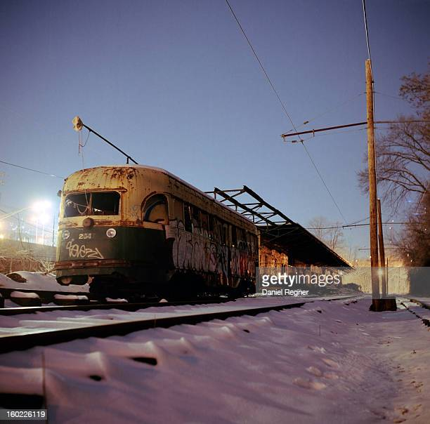 Shot of an old rusted train on the train tracks, out of commission and use for many years. It is gathering rust in the snow and winter cold. Graffiti...