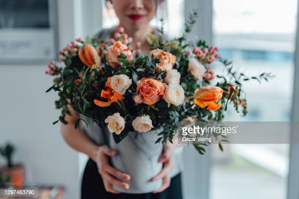 shot of an unrecognisable woman covering her face with flowers in living room - anniversary stock pictures, royalty-free photos & images